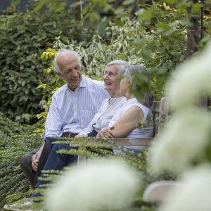 Elderly people sitting on a bench in the gardne