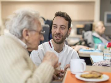 A nurse talking to an elderly man having breakfast